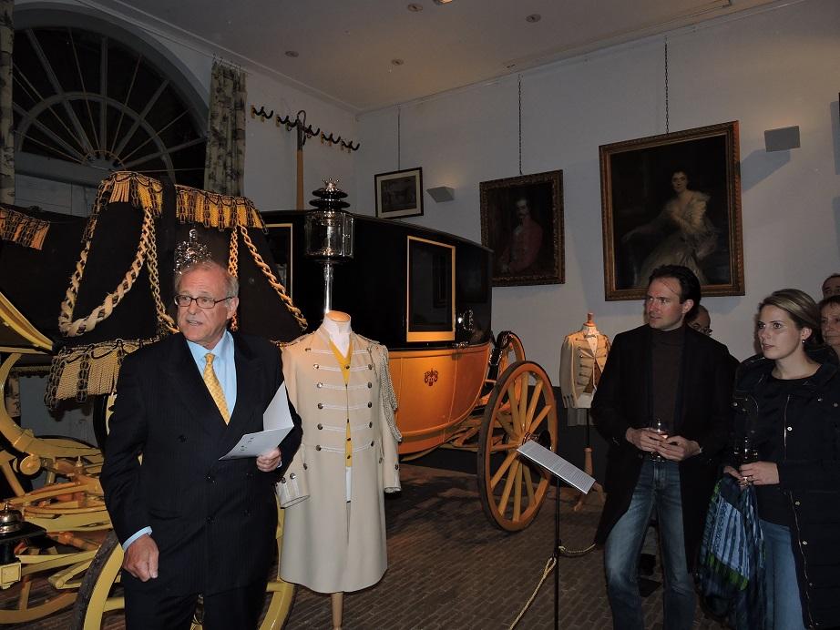 Afb. 1. De heer Swane, achterkleinzoon van jonkheer Louis Antoine van Loon en Adèle Françoise van Loon-Tachard, staat voor de gala-berline van zijn overgrootouders met hun portretten op de achtergrond en vertelt over hun leefwijze.