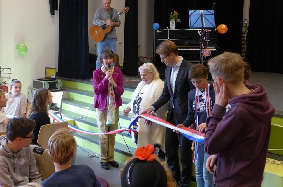 Afb. 1. Staatssecretaris Sander Dekker bij de eerste adoptiedag van het Maerlant Lyceum met links achter de microfoon Ilona van Voorst tot Voorst.