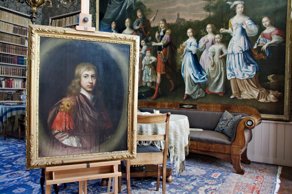 Afb. Het portret van Edzard Jacob Tjarda van Starkenborgh met achter hem het grote familieportret, waarop hij prominent in het midden staat afgebeeld. Foto met hartelijke dank aan landgoed Verhildersum.