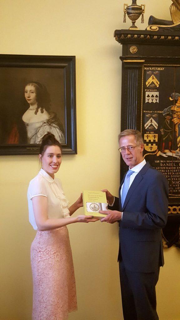 Afb. Dr. Sophie Reinders overhandigt haar boek aan mr. Marc Scheidius, de secretaris van de Hoge Raad van Adel.